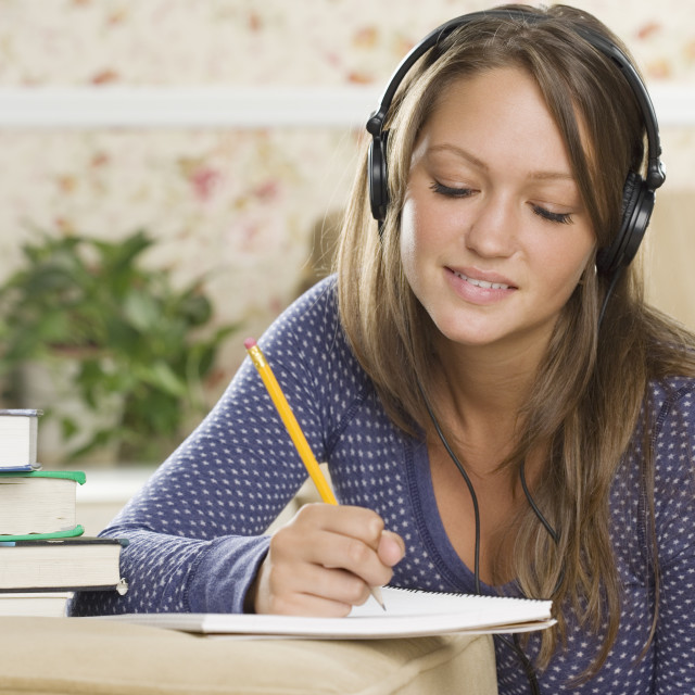 """Young woman wearing headphones and doing homework"" stock image"