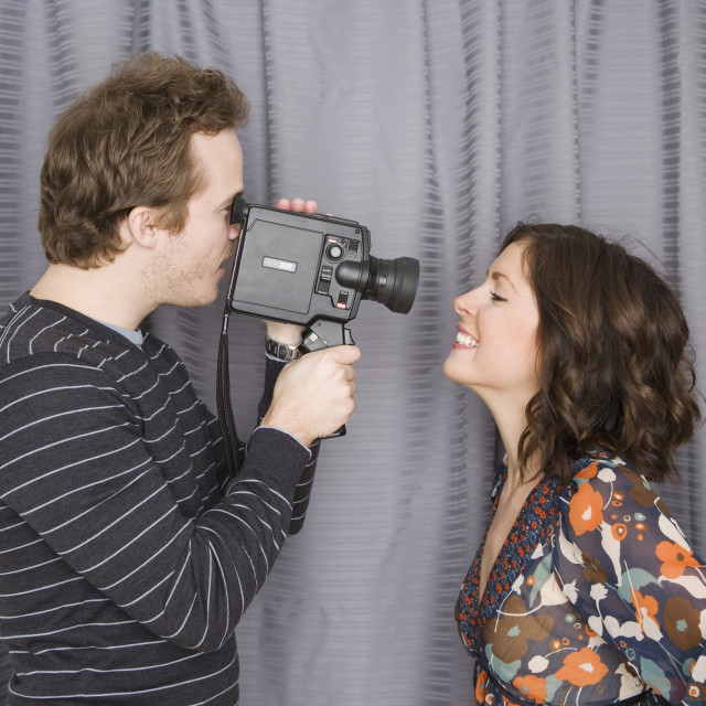 """Man video recording girlfriend's face"" stock image"