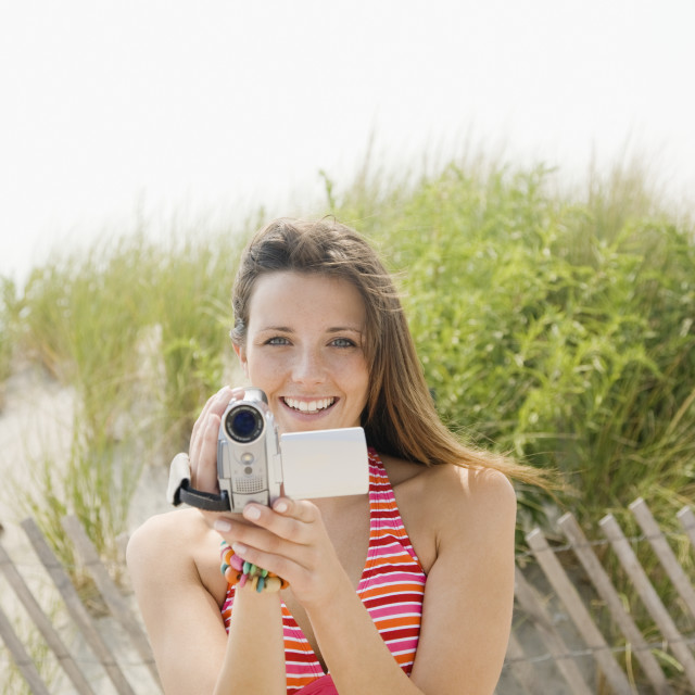 """Woman holding video camera at beach"" stock image"