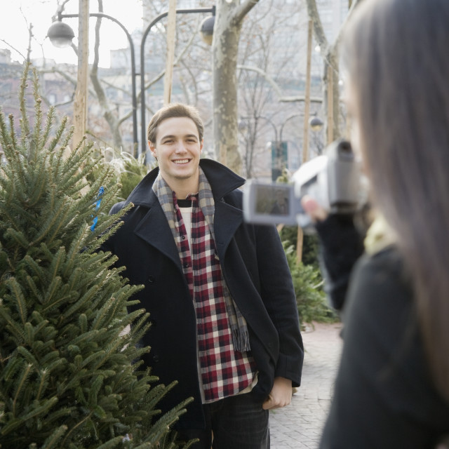 """Woman video recording boyfriend with Christmas tree"" stock image"