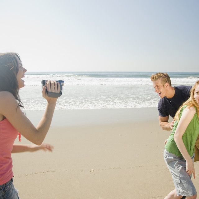"""Woman video recording friends at beach"" stock image"