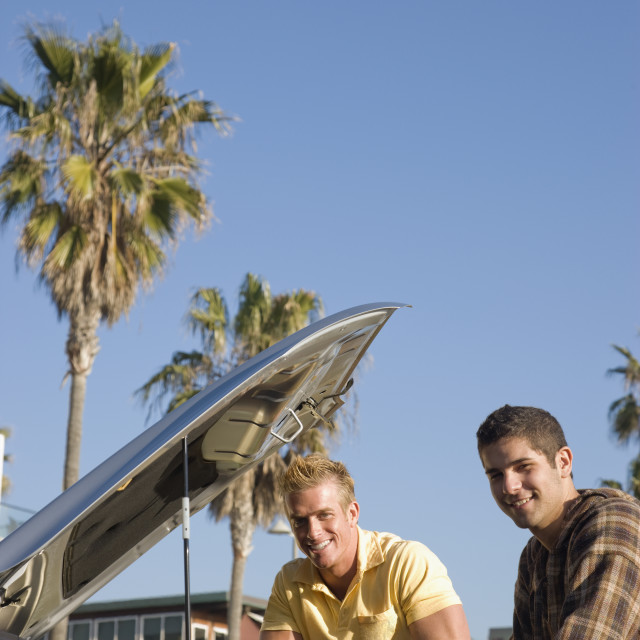 """Two men looking under car hood"" stock image"
