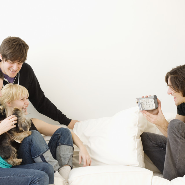 """Man video recording friends on sofa"" stock image"