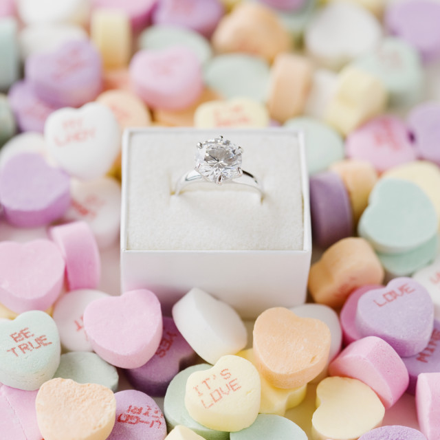 """Engagement ring in box on candy hearts"" stock image"
