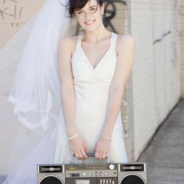 """Portrait of bride holding stereo in street"" stock image"
