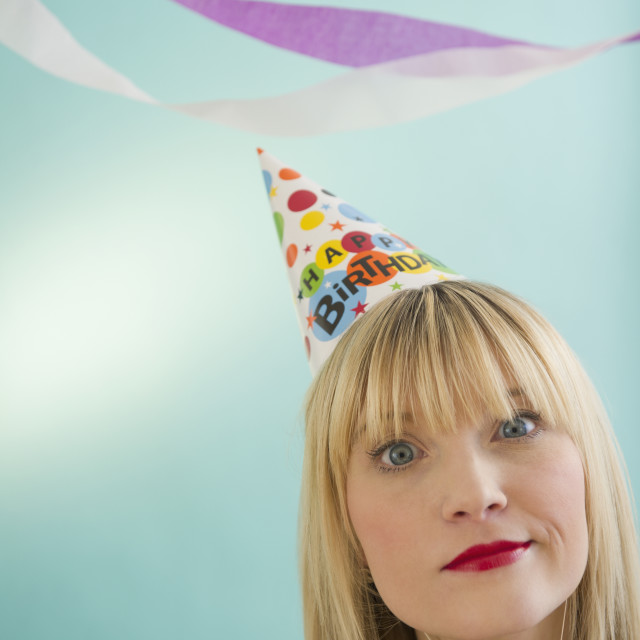 """Young woman wearing party hat smirking"" stock image"