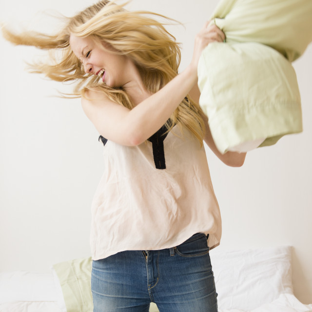 """Young woman kneeling on bed and throwing pillow"" stock image"