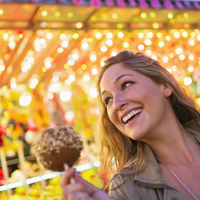 """Woman holding caramel apple at funfair"" stock image"