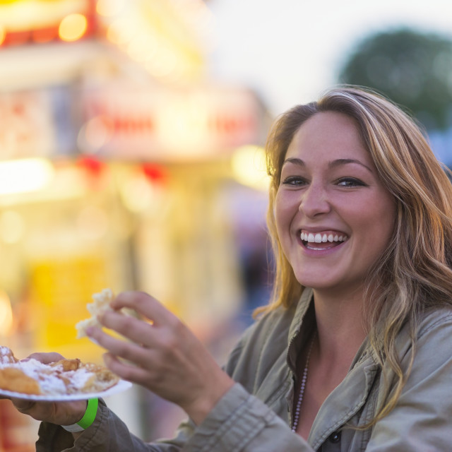 """Woman eating funnel cake at funfair"" stock image"