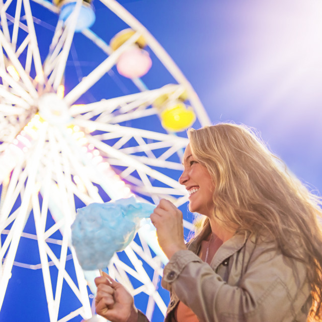 """Woman holding cotton candy at funfair"" stock image"