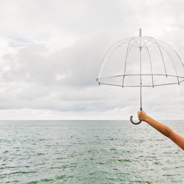 """Person holding umbrella against cloudy sky"" stock image"