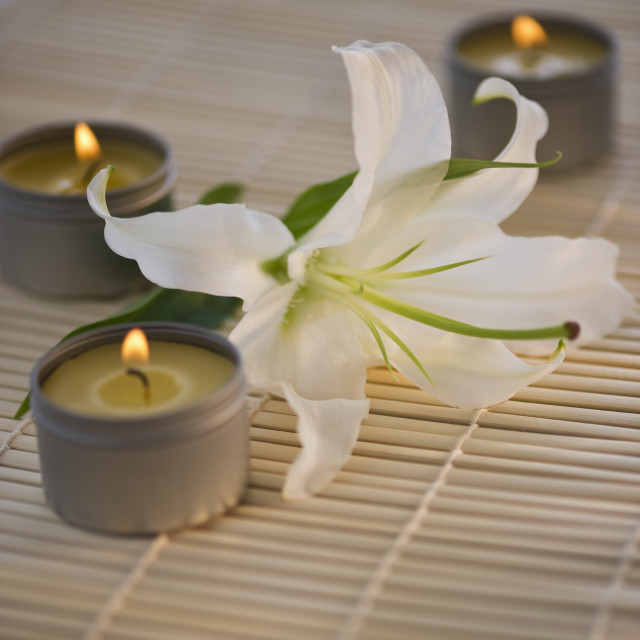"""Tea lights and white lily on bamboo mat"" stock image"