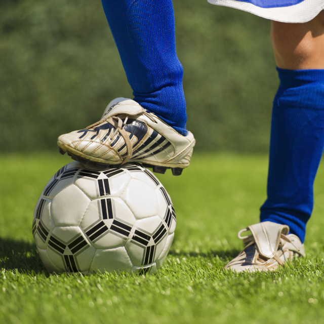 """""""Low section of boy (10-11) playing soccer"""" stock image"""