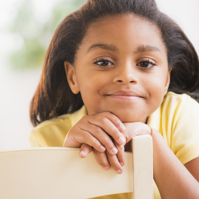 """""""Portrait of smiling girl (6-7) sitting on chair"""" stock image"""