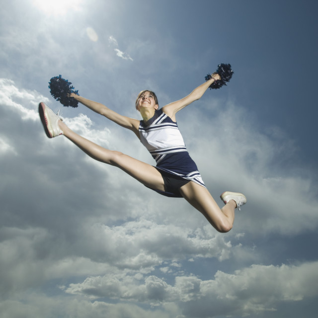 """""""Low angle view of cheerleader jumping"""" stock image"""
