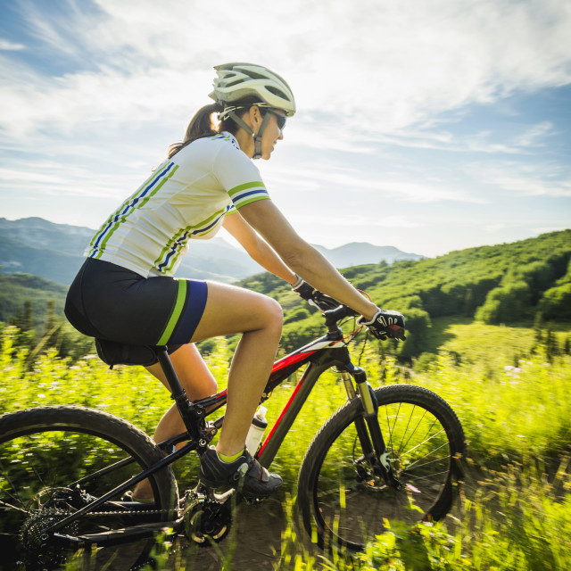 """""""Woman during bicycle trip in mountain scenery"""" stock image"""