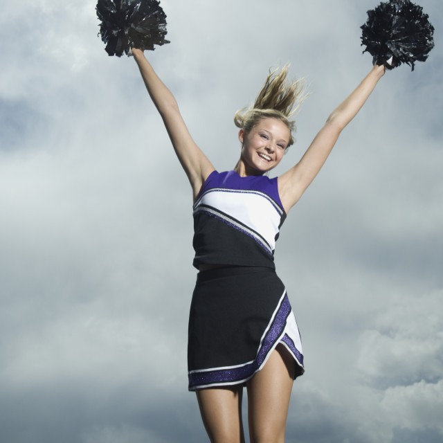 """Cheerleader with pom poms jumping"" stock image"