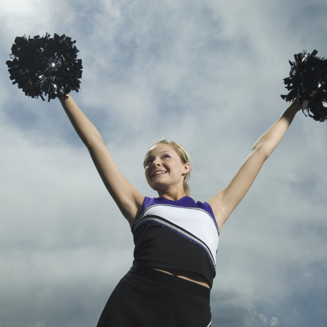 """Cheerleader holding pom poms over head"" stock image"