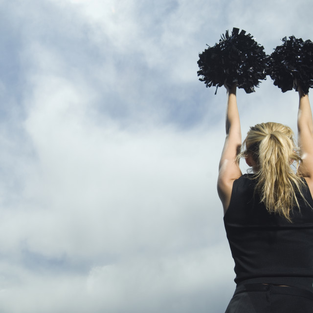"""Rear view of cheerleader with pom poms"" stock image"