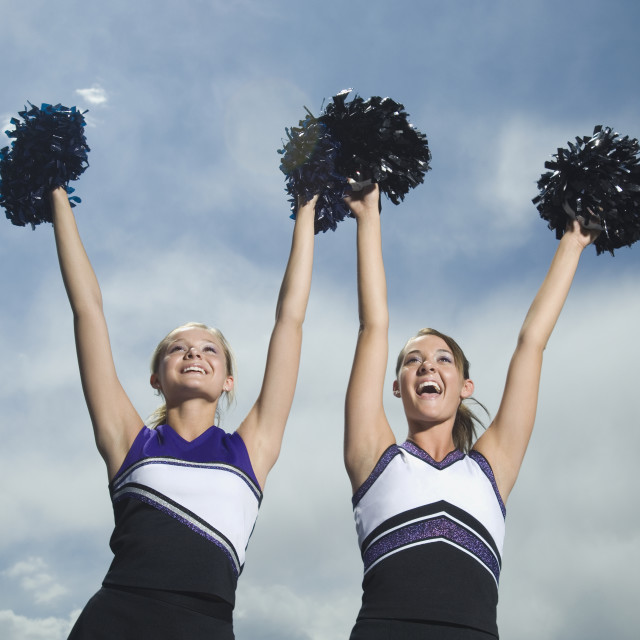 """Two cheerleaders holding pom poms over head"" stock image"