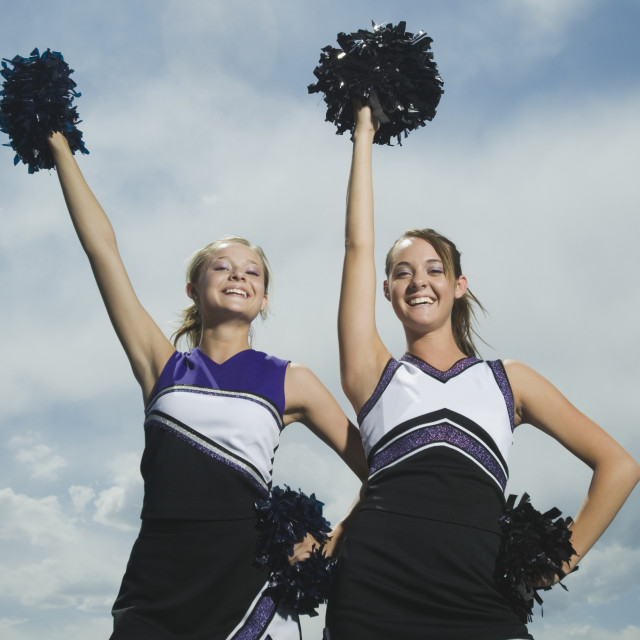 """Two cheerleaders holding pom poms"" stock image"