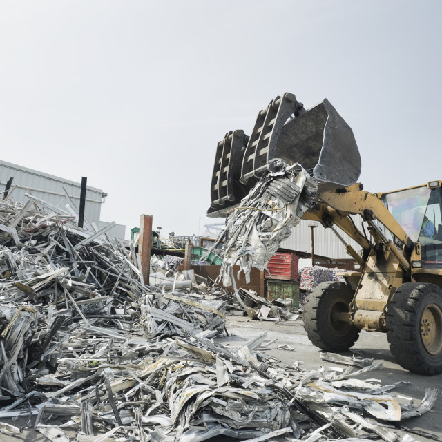 """""""Backhoe dumping recyclable metal"""" stock image"""