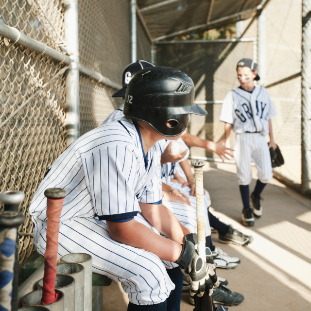 """USA, California, Ladera Ranch, Boys (10-11) from little league sitting on dugout"" stock image"