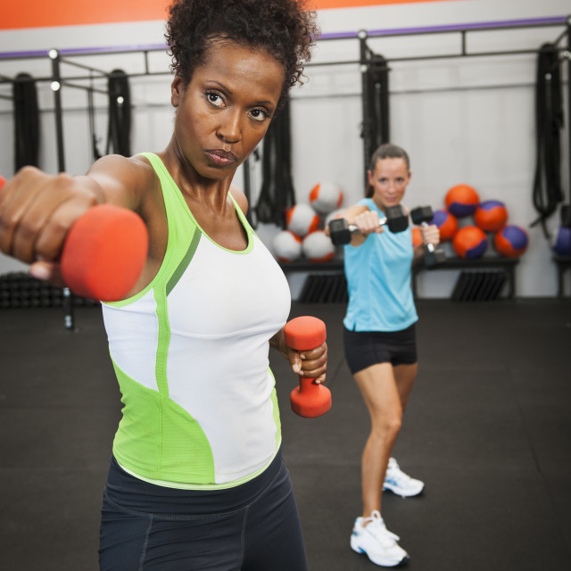 """""""Two mid adult women exercising with dumbbells"""" stock image"""