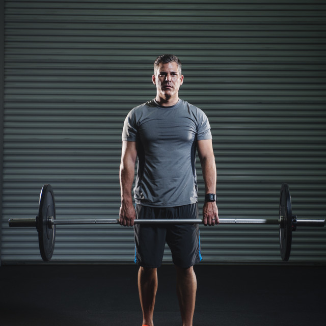 """Mature man lifting heavy barbell"" stock image"