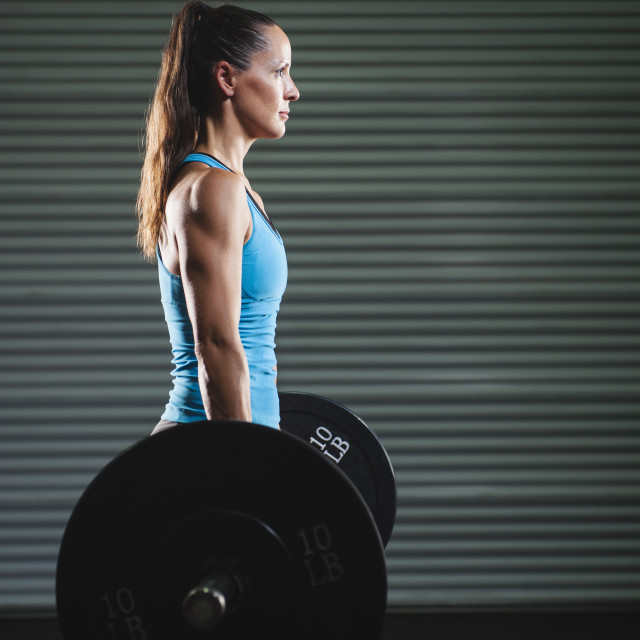 """mid adult woman lifting barbell"" stock image"