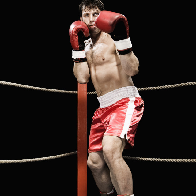 """Boxer standing in fighting stance in boxing ring"" stock image"