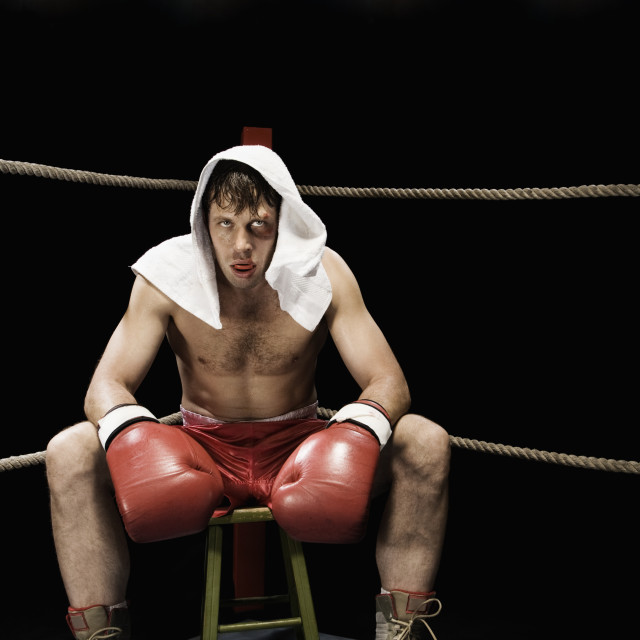 """Boxer sitting on stool in corner of boxing ring"" stock image"