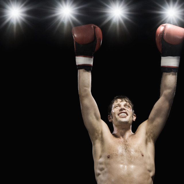 """Boxer smiling with boxing gloves raised"" stock image"