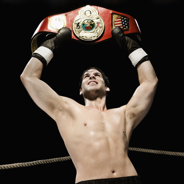 """Boxer holding championship belt overhead in boxing ring"" stock image"