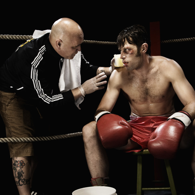 """Coach talking to boxer in corner of boxing ring"" stock image"