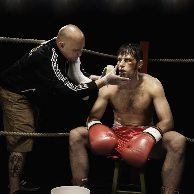 """Coach wiping boxer with sponge in corner of boxing ring"" stock image"