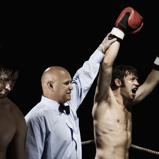 """Referee standing between winning and losing boxers"" stock image"