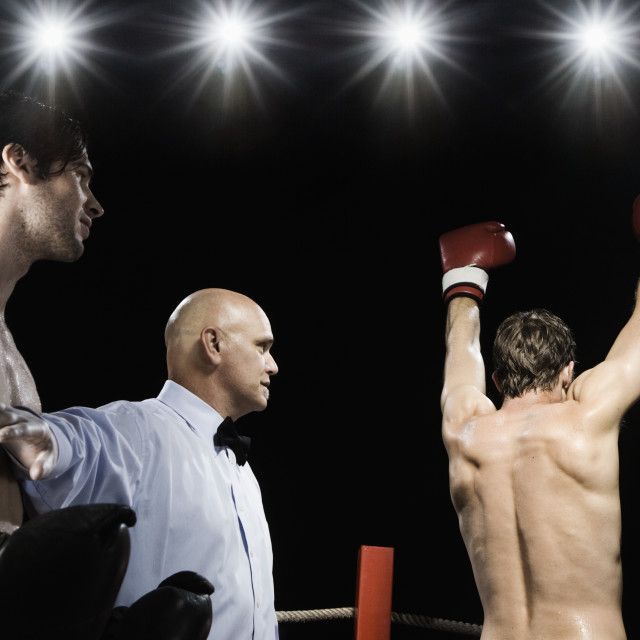 """Referee holding losing boxer back from winner"" stock image"