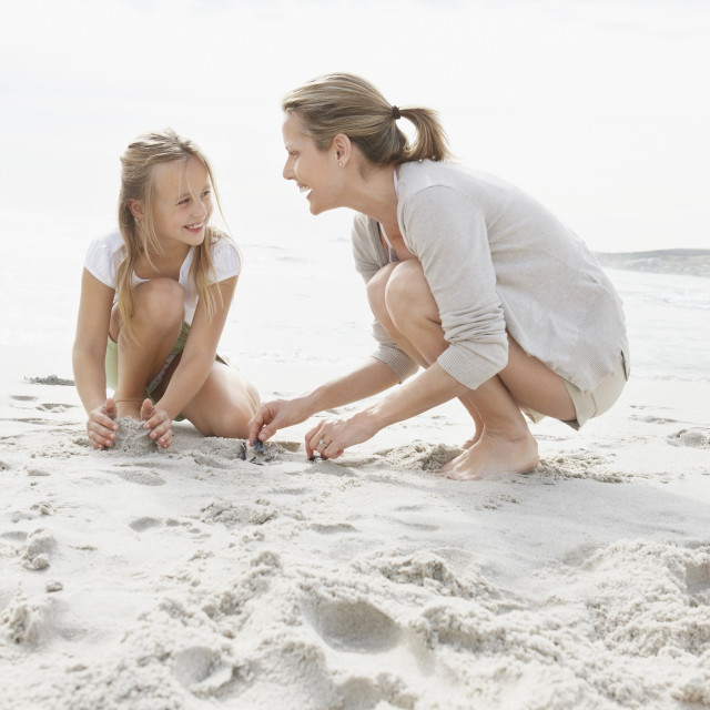 """""""Girl (10-11) playing on beach with mother"""" stock image"""