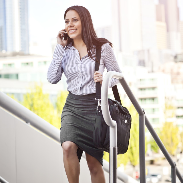 """USA, Washington, Seattle, Young businesswoman walking up steps talking on phone"" stock image"