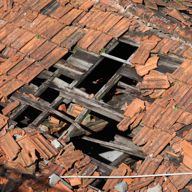 """Hole in Damaged Tiled Roof"" stock image"