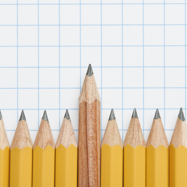 """Single wooden pencil rising above row of sharpened pencils on graph paper, studio shot"" stock image"
