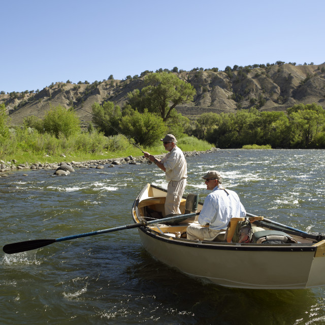 """USA, Colorado, Pair of men fly-fishing on mountain river"" stock image"