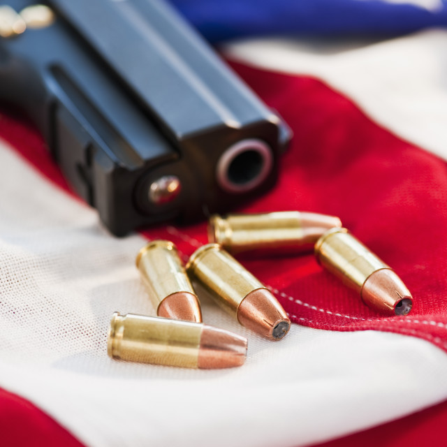 """A handgun and ammunition on the American flag"" stock image"