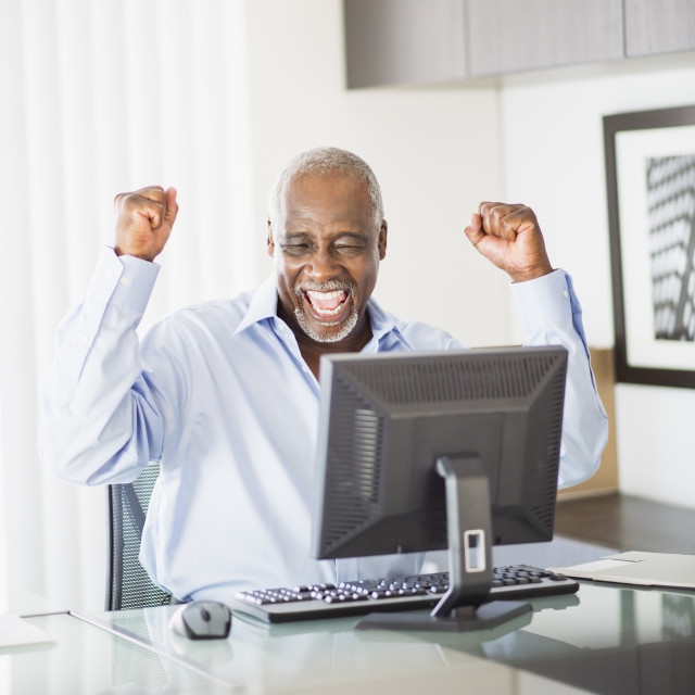 """Portrait of satisfied senior man in office"" stock image"