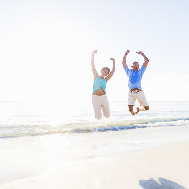 """Mature couple jumping in sea with arms raised"" stock image"