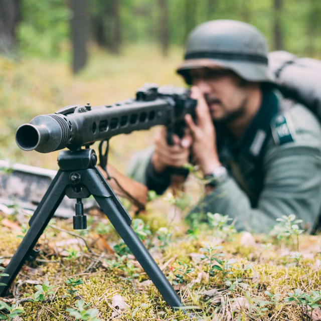"""""""Hidden unidentified re-enactor dressed as german wehrmacht soldier aiming a..."""" stock image"""