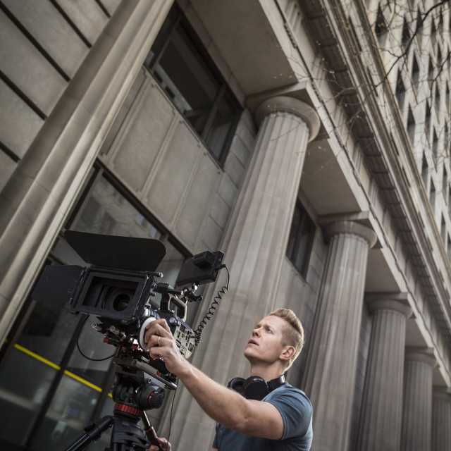 """""""Camera operator filming in front of building"""" stock image"""