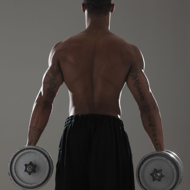 """""""Physically fit man lifting dumbbells"""" stock image"""