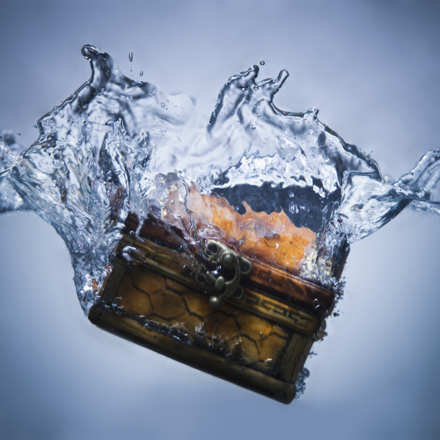 """Treasure chest sinking in water"" stock image"